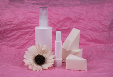 Бутылка набора косметик с губкой и цветок на розовой предпосылке стоковая фотография
