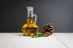 Бутылка оливкового масла, свежей ветви розмаринового масла и конуса сосны на белом деревянном столе Стоковые Фото