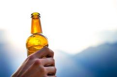 Бутылка пива Естественная предпосылка Handчеловека держат бутылку пива Питье спирта Стоковое Изображение