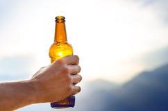 Бутылка пива Естественная предпосылка Handчеловека держат бутылку пива Питье спирта Стоковое фото RF