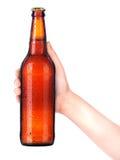 Бутылка пива при рука человека делая изолированную здравицу на белизне Стоковое Изображение