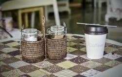 Бутылка сахара в бамбуковой кофейной чашке корзины и бумаги дальше Стоковые Фото