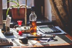 Бутылка спирта и часов на вашем настольном компьютере стоковые изображения rf