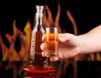 Бутылка, стеклянная водочка перца в руке на предпосылке пылает Стоковое Изображение RF