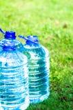 Бутылка с водой бутылки с водой пластичная на траве Стоковая Фотография