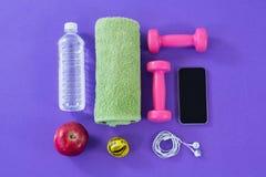 Бутылка с водой, полотенце, измеряя лента, гантели, яблоко, мобильный телефон и наушники Стоковые Изображения RF