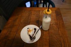 Бутылка с молоком в котором черная выпивать солома, на которую положите Стоковые Фотографии RF