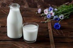 Бутылка с молоком и стеклом молока на деревянном столе Стоковое Фото