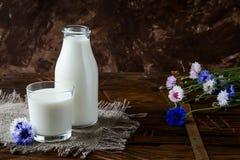 Бутылка с молоком и стеклом молока на деревянном столе Стоковые Фотографии RF