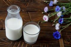 Бутылка с молоком и стеклом молока на деревянном столе Стоковые Изображения