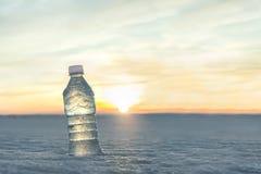 Бутылка холодной воды в снеге на заходе солнца стоковые фотографии rf