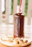Бутылка черного замороженного кофе с некоторой закуской стоковое изображение
