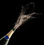 Бутылка Шампани с выплеском стоковые изображения
