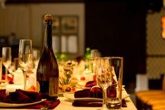 Бутылка шампанского и каннелюры на официально таблице Стоковые Изображения RF