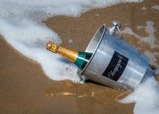 Бутылка шампанского на песчаном пляже Стоковые Фотографии RF