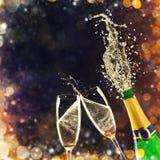 Бутылка шампанского с стеклами над предпосылкой фейерверков стоковое изображение