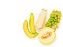 Бутылка дыни, виноградин, сока банана изолированного на белизне Стоковое Фото