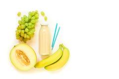 Бутылка дыни, виноградин, сока банана изолированного на белизне Стоковая Фотография