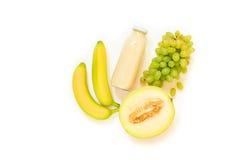 Бутылка дыни, виноградин, сока банана изолированного на белизне Стоковые Фотографии RF