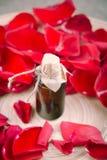 Бутылка эфирного масла и красные розы, вода дух Стоковое Фото