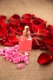 Бутылка эфирного масла и красные розы, вода дух Стоковые Изображения