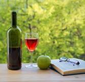 Бутылка eyeglasses и книги яблока зеленого цвета вина на таблице Стоковое Фото