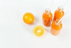 3 бутылки апельсинового сока и трубок на таблице на белой предпосылке Стоковые Изображения