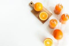3 бутылки апельсинового сока и трубок на таблице на wh Стоковая Фотография