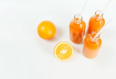 3 бутылки апельсинового сока и трубок на таблице на wh стоковые изображения rf