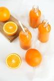 3 бутылки апельсинового сока и трубок на таблице Стоковое Изображение RF
