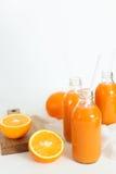 3 бутылки апельсинового сока и трубок на таблице Стоковые Изображения RF