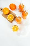 3 бутылки апельсинового сока и трубок на таблице Стоковое Фото
