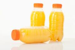 Бутылки апельсинового сока на белой предпосылке, конце вверх Стоковое Изображение RF