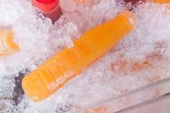 Бутылки апельсинового сока на коробке льда Стоковые Изображения RF