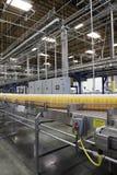Бутылки апельсинового сока на транспортере в заводе по розливу Стоковые Изображения