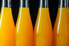 Бутылки апельсинового сока на черной предпосылке Стоковые Изображения RF