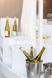 Бутылки белого вина стоя на таблице сервировки Внешняя партия, ресторанное обслуживание Стоковое фото RF