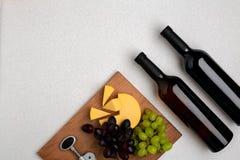 2 бутылки белого и красного вина, сыра и виноградин Взгляд сверху Стоковое фото RF