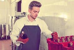 Бутылки вина мужского работника упаковывая на фабрике игристого вина Стоковая Фотография