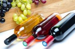 Бутылки вина перед деревянной коробкой с виноградинами Стоковые Изображения RF