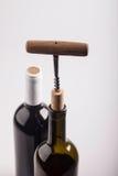 2 бутылки вина, пробочка и штопора на белой предпосылке Стоковая Фотография RF