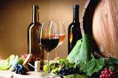 Бутылки вина, стекла, виноградины и бочонок Стоковые Изображения RF