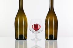 2 бутылки и красного сердце внутри стекла коньяка Стоковая Фотография RF