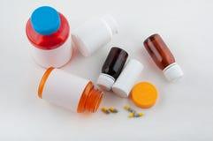 Бутылки и пилюльки другого цвета фармацевтические кладя на белую таблицу Стоковые Фото