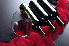 Бутылки и стекло красного вина на черной таблице Стоковая Фотография RF