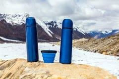 2 бутылки и чашка голубых thermoses перемещения термо- на камне Стоковые Фотографии RF