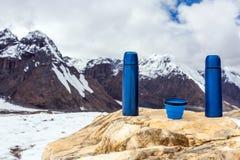 2 бутылки и чашка голубых thermoses перемещения термо- на камне Стоковое Изображение