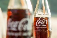 2 бутылки кока-колы с английскими и тайскими ярлыками сравнены в Ao Nang, Таиланде Стоковые Фотографии RF