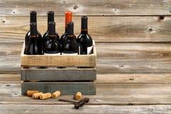 Бутылки красного вина в деревянной клети на деревенских деревянных досках Стоковое Изображение RF