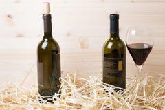 2 бутылки красного вина и бокала в соломе Стоковое фото RF